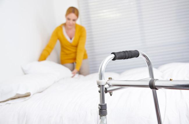Seniors facility walker and caregiver preparing bed sheets